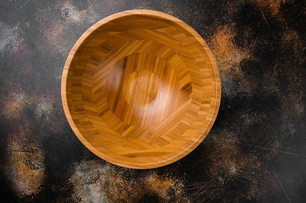 Drewniana miska z miejscem na kopię na tekst lub jedzenie, widok z góry płasko leżący, na starym ciemnym, rustykalnym tle stołu