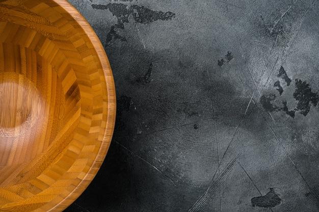 Drewniana miska z miejscem na kopię na tekst lub jedzenie, widok z góry płasko leżący, na szarym tle kamiennego stołu