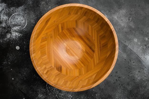 Drewniana miska z miejscem na kopię tekstu lub jedzenia, widok z góry płasko leżący, na czarnym ciemnym tle kamiennego stołu