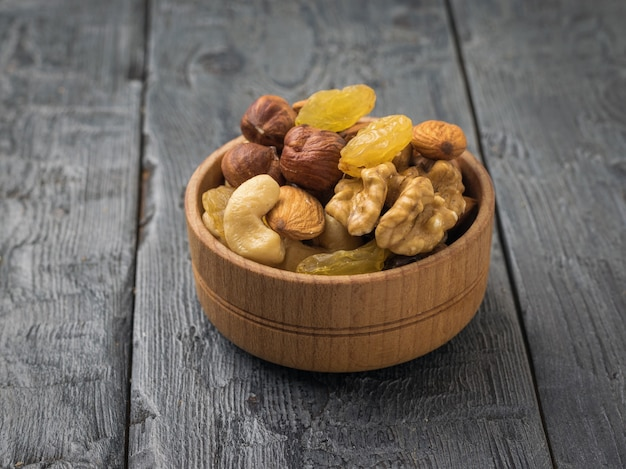 Drewniana miska z mieszanką orzechów i suszonych owoców na czarnym drewnianym stole. naturalne zdrowe jedzenie wegetariańskie.