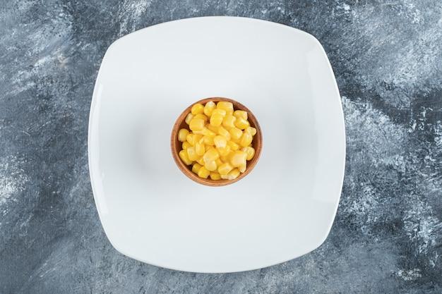 Drewniana miska z nasionami popcornu na pustym talerzu.