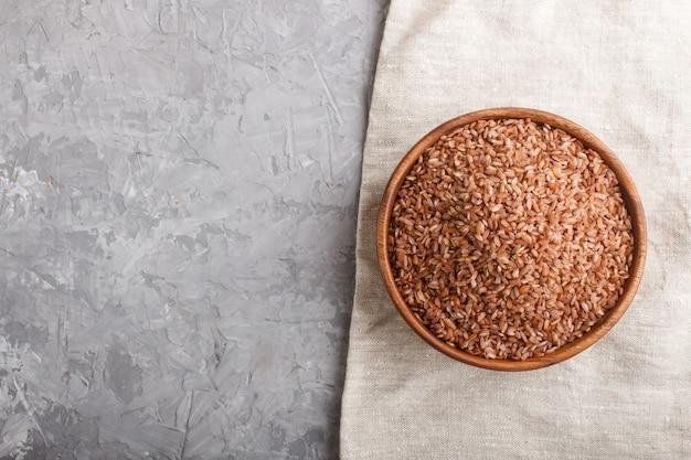Drewniana miska z nieoszlifowanym brązowym ryżem na szarym tle betonu. widok z góry, miejsce.
