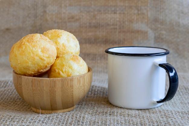 Drewniana miska z pieczywem serowym i kubkiem białej kawy