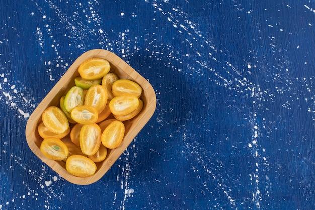 Drewniana miska z pokrojonymi świeżymi owocami kumkwatu na marmurowej powierzchni.