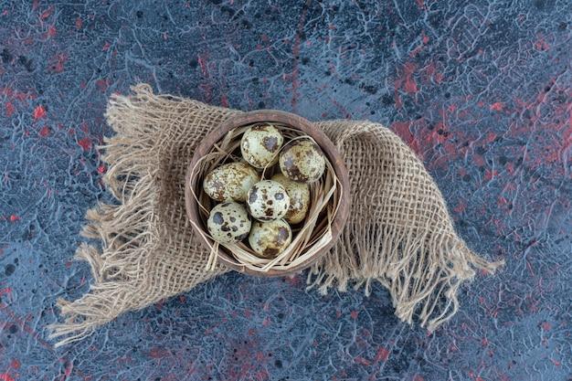 Drewniana miska z przepiórczymi jajkami na worze.