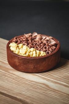 Drewniana miska z różnymi rodzajami szybkich produktów śniadaniowych