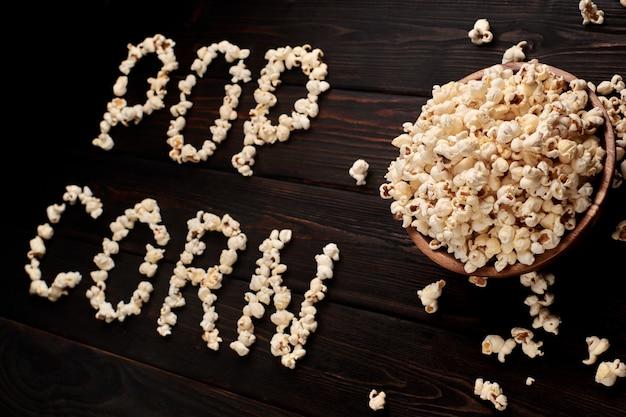 Drewniana miska z słonym popcornem na drewnianym stole. ciemne tło selektywne ustawianie ostrości. leżał płasko. u автор: ugryumov igor
