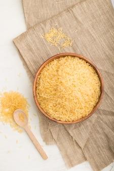 Drewniana miska z surowym złotym ryżem i drewnianą łyżką na białym drewnianym stole i lnianej tkaninie. widok z góry, leżał na płasko, z bliska.