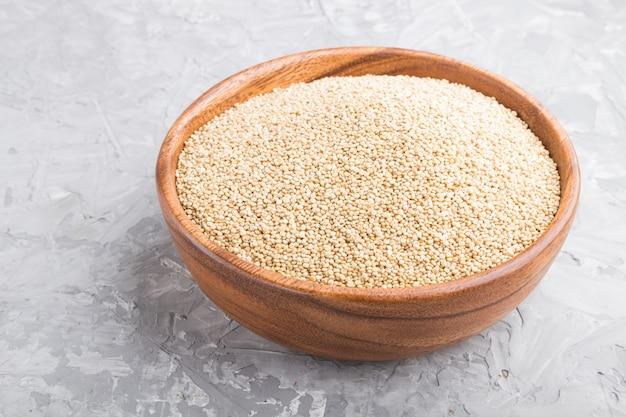 Drewniana miska z surowymi białymi nasionami komosy ryżowej na szarym betonowym stole. widok z boku, z bliska.