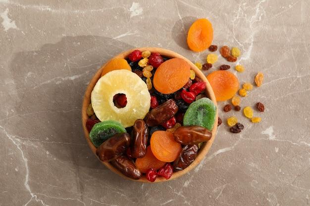 Drewniana miska z suszonymi owocami na szaro
