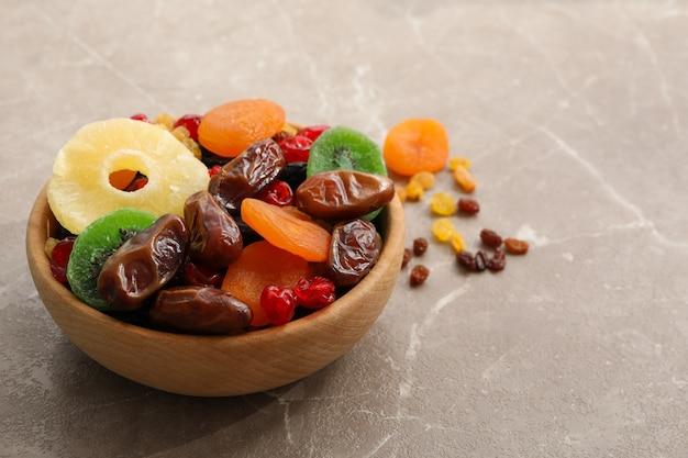 Drewniana miska z suszonymi owocami na szarym stole