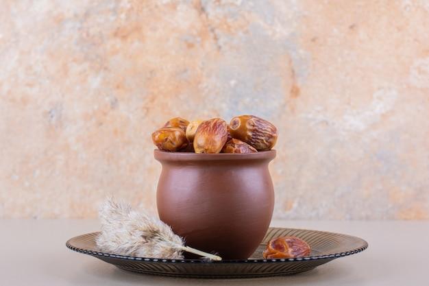 Drewniana miska z suszonymi smacznymi daktylami na białym tle. wysokiej jakości zdjęcie
