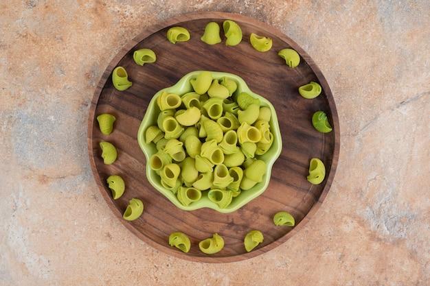 Drewniana miska z zielonym talerzem zielonego, nieprzygotowanego makaronu.