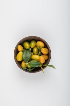Drewniana miska z żółtymi kumkwatami z liśćmi na białym.