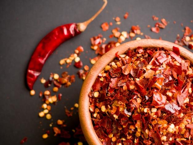 Drewniana miska zmiażdżonego czerwonego pieprzu, pieprzu cayenne, suszonego chili