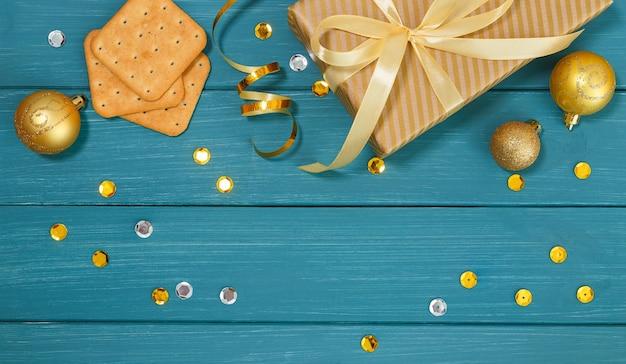 Drewniana niebieska powierzchnia ze złotymi dekoracjami świątecznymi, krakersami i pudełkiem prezentowym