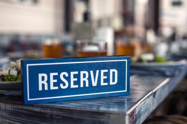 Drewniana niebiesko-biała prostokątna płytka z napisem reserved stoi na rogu szarego, starodawnego stołu. koncepcja lunchu w restauracji, wakacje, bankiet