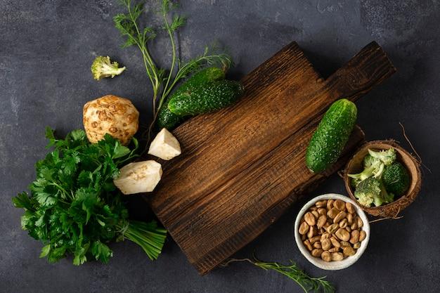 Drewniana nieociosana tnąca deska z składnikami dla gotować weganinu jedzenie na ciemnego tła odgórnym widoku