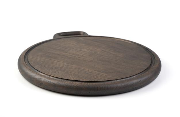 Drewniana okrągła deska do krojenia wykonana z materiału dębowego, pomalowana na ciemny kolor, izolowana. obiekt do wykorzystania w projekcie. pojęcie gotowania.