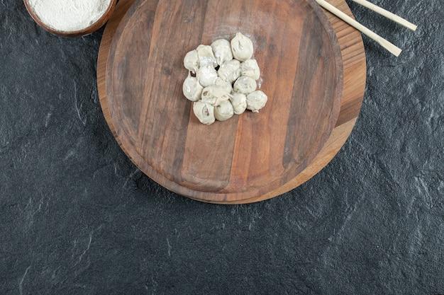 Drewniana okrągła deska z niegotowanymi kluskami i mąką.