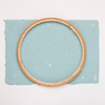 Drewniana okrągła rama na niebieskim papierze na białym tle