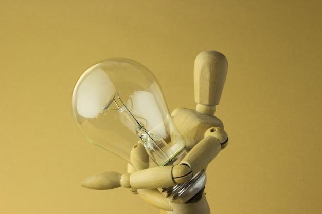 Drewniana osoba trzyma elektryczną żarówkę w ręce