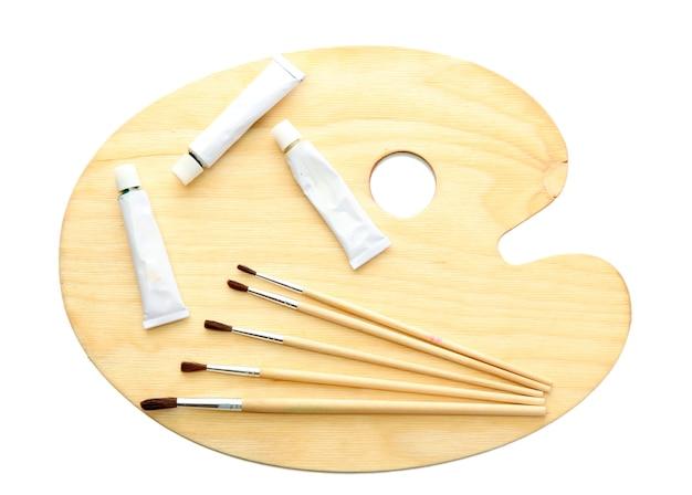 Drewniana paleta sztuki, tubki z farbą i pędzle na białym tle