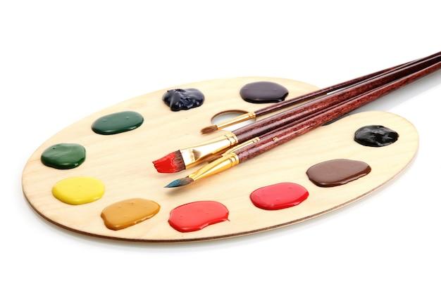 Drewniana paleta sztuki z farbą i pędzlami na białym tle