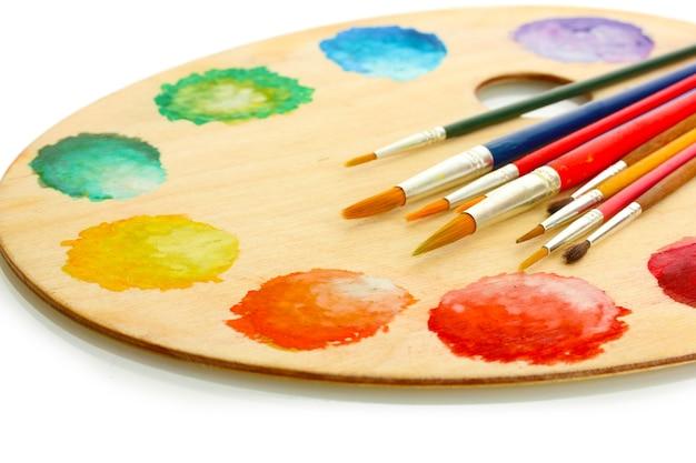 Drewniana paleta sztuki z farbą i pędzlami na białym