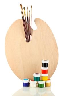 Drewniana paleta sztuki z pędzlami do malowania i farb na białym tle
