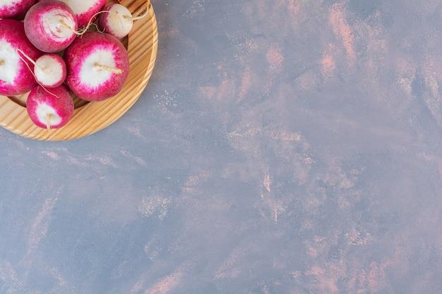 Drewniana płyta latem zebrane czerwone świeże rzodkiewki na tle kamienia.
