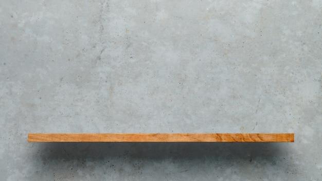 Drewniana półka nad białym betonowej ściany tłem
