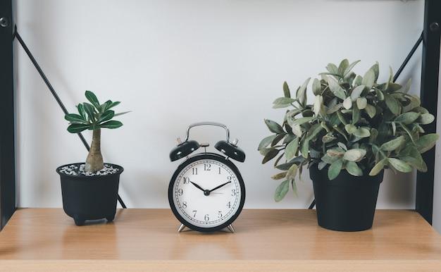Drewniana półka z bukietem suchych kwiatów, trawą w doniczce, zielenią w wazonie i alarmem nad białą dekoracją ścienną w salonie w domu