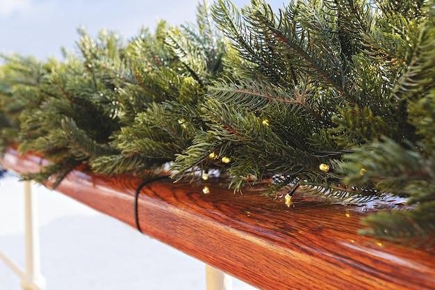 Drewniana poręcz ozdobiona jodłową girlandą i lampkami choinkowymi. wystrój zewnętrzny w okresie świątecznym