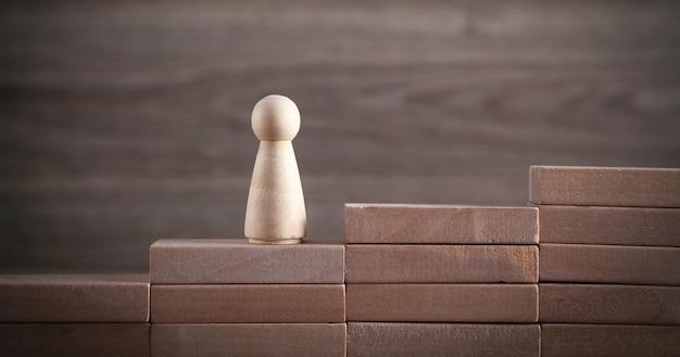 Drewniana postać ludzka na schodach. biznes. kariera zawodowa