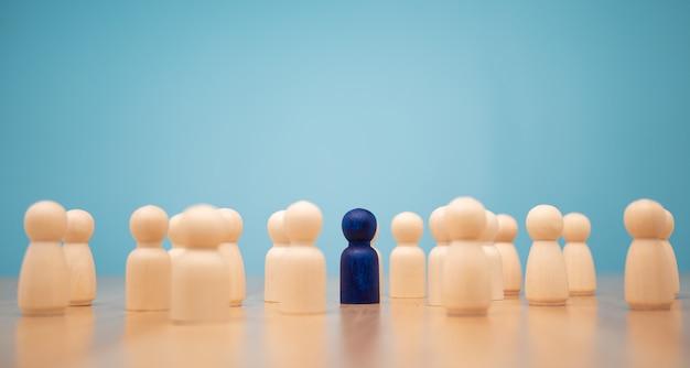 Drewniana postać stojąca z drużyną, aby pokazać wpływy i wzmocnienie.