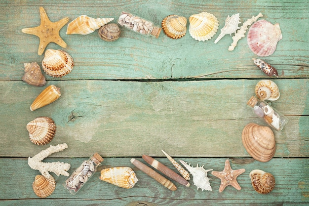 Drewniana powierzchnia morska z ramą z muszelek, rozgwiazd, przegrzebków i małych butelek