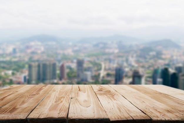 Drewniana powierzchnia na rozmytym tle nieba w górach miasta