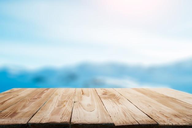 Drewniana powierzchnia na rozmytym tle śnieżnego górzystego obszaru w zimowy dzień i błękitne niebo
