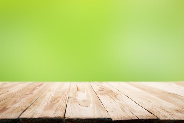 Drewniana powierzchnia na zamazanym zielonym tle