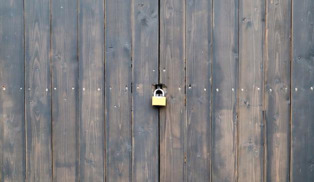 Drewniana powierzchnia starych teksturowanych brązowych desek zamkniętych na zardzewiały zamek z bliska. stara drewniana brama z metalowym zamkiem. brązowe drewniane drzwi z zamkiem.