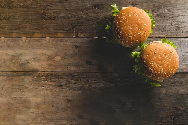 Drewniana powierzchnia z dwoma apetycznymi hamburgery