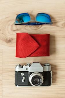 Drewniana powierzchnia z krawatem, okulary słoneczne i aparat fotograficzny