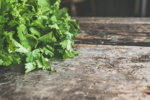 Drewniana powierzchnia z miejscem na tekst z zielonymi liśćmi pietruszki z boku