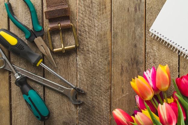 Drewniana powierzchnia z narzędziami, kwiatami i notatnikiem na dzień ojca