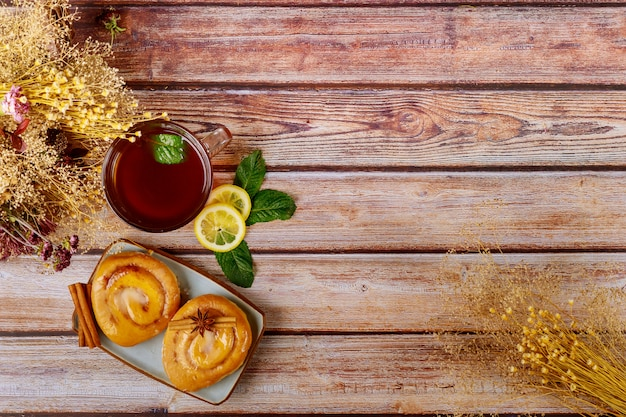 Drewniana powierzchnia z przeszklonymi bułeczkami cynamonowymi i filiżanką herbaty z cytryną i miętą