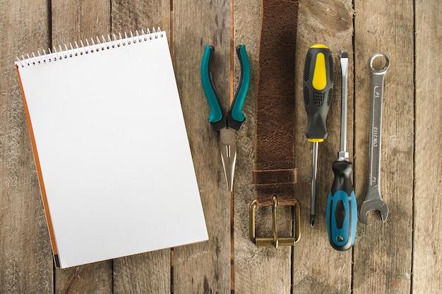 Drewniana powierzchnia z pustym notatnikiem i narzędziami dekoracyjnymi