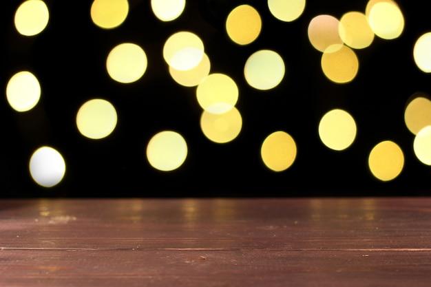 Drewniana powierzchnia z żółtymi światłami bokeh