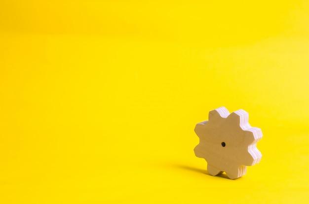 Drewniana przekładnia na żółtym tle. pojęcie technologii i procesów biznesowych.