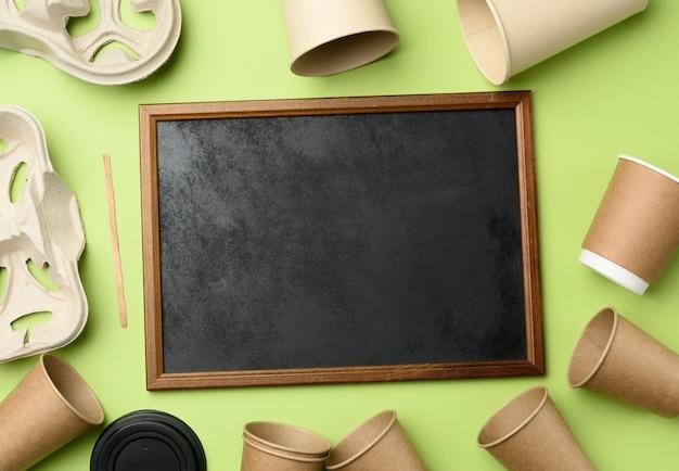 Drewniana rama i jednorazowe kubki papierowe z brązowego papieru rzemieślniczego i pojemniki na papier z recyklingu